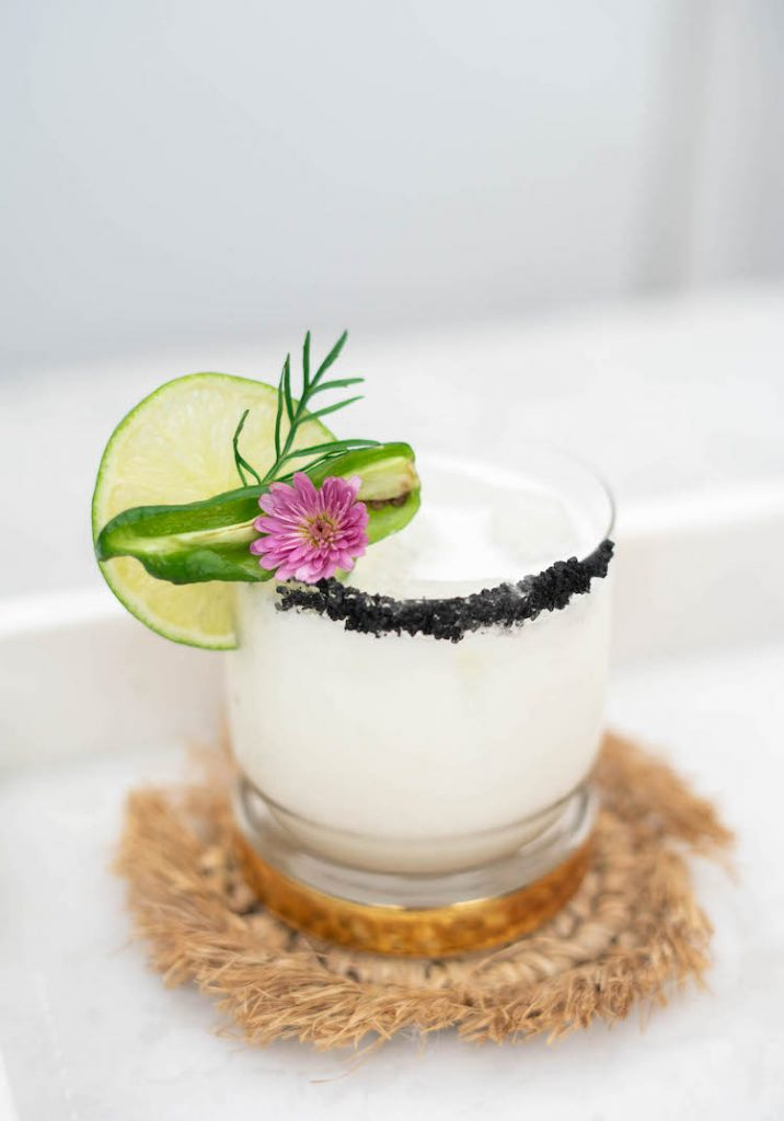 This Coconut Jalapeño Margarita is a spicy, tropical twist on the classic tequila cocktail. Black lava salt adds a striking rim to the white drink. Spicy jalapeño is tempered by cooling coconut for a refreshing, but zippy sip for Cinco De Mayo or any day of the year.